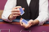 Dealer shuffling deck of cards while sitting at table of a casino