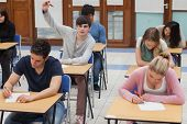 Student raising hand during exam in exam hall in college