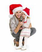 Retrato de Natal da feliz mãe e bebê menina cantar em Mi