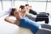 Três mulheres fazer Sit-ups nas bolas de exercício no ginásio