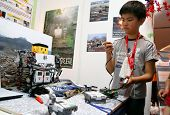 SUBANG JAYA - NOVEMBER 10: An unidentified students from Japan tests his remote control robot made t