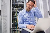 Technician getting frustrated with laptop over servers in data center