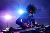 image of club party  - nightclub dj playing music on deck with vinyl record headphones light flare clubbing party scene - JPG