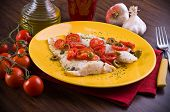 Fish fillet with cherry tomatoes and olive.