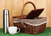 metal thermos with cup and basket on grass on wooden background
