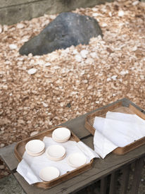 stock photo of atonement  - oriental atonement ceremony with small ceramic saucers and big boulder - JPG