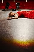 Beautiful young woman in red gown lying on stage floor