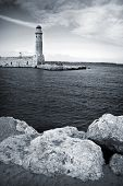 Old Venetian Lighthouse Of Rethimno With Rocks Coast On Foreground. Island Crete, Greece.