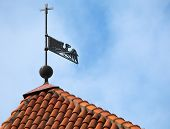 Vintage Weather Vane Bird On The Red Roof Above Blue Sky. Old Part Of Tallinn, Estonia