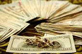 Dollar Notes And Gold Rings Over Tablecloth