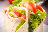 stock photo of sandwich wrap  - Tasty tortilla sandwich wrap with turkey and vegetables - JPG