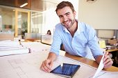 stock photo of blueprints  - Male Architect With Digital Tablet Studying Plans In Office - JPG