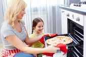 Portrait of happy young woman taking pizza out of oven, her daughter standing near by