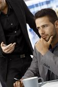 Closeup portrait of working, concentrating businessman sitting at desk, colleague standing by him, t