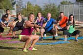 stock photo of squatting  - Mixed group of people doing a boot camp exercise class
