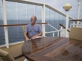Man Sitting At A Table On A Cruise Ship Taking In The View