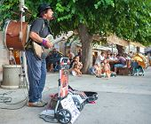 VIS, CROATIA - AUGUST 19, 2012:  Street musician plays guitar, drum and mouth organ.
