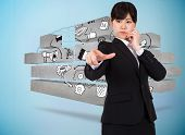 Businesswoman pointing against faint brain on blue background