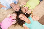 Smiling family lying on the rug in a circle showing thumbs up at home in living room