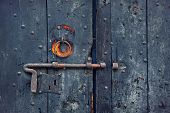 Closeup image of old wooden door with metal knob and rusty bolt.