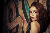 Teenager on graffiti background. Girl against painted wall.urban style