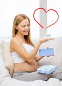 pregnancy, motherhood and celebration concept - smiling pregnant woman sitting on sofa with gift box