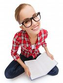 education and leisure concept - smiling teenage girl in black eyeglasses reading book