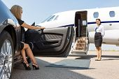 stock photo of superstars  - Elegant woman stepping out of car parked in front of private plane and airhostess - JPG