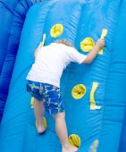 stock photo of inflatable slide  - Young boy climbing higher on water slide