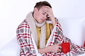 Guy wrapped in plaid lies on sofa on white background