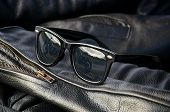 foto of motorcycle  - close up generic wayfarer sunglasses on sleeve of buffalo hide motorcycle jacket showing motorcycle in reflection - JPG
