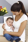 stock photo of lap  - Young mother holding baby boy on lap - JPG