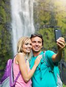 Couple having fun together outdoors. Taking self portrait with camera phone after hiking to incredible waterfall in Hawaii.