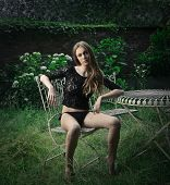 beautiful woman sitting on an elegant chair in the garden