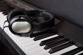 Close-up black headphones on digital  piano keyboard