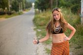Young hippie girl hitch hiking on countryside road.