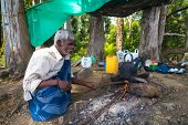 ELLA, SRI LANKA - MARCH 2, 2014: Elderly local man boiling water in a pot on camp fire in forest.