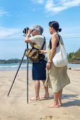 WELIGAMA, SRI LANKA - MARCH 7, 2014: Japanese tourists stand on sandy beach and take photos with old