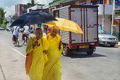 HIKKADUWA, SRI LANKA - MARCH 4, 2014: Buddhist nuns in yellow robes walk on street of Hikkaduwa. Gangarama Maha Vihara Buddhist temple is worth a visit to experience Hikkaduwa's cultural side