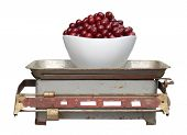 Red Cherry In A White Cup On Old Mechanical Scales Isolated On White Background.