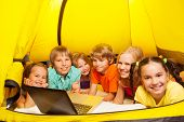 Six kids lay in a yellow tent