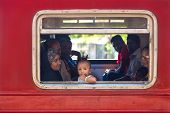 HIKKADUWA, SRI LANKA - MARCH 12, 2014: Local people in train looking through window. Trains are very