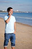 image of mobile-phone  - Man with a mobile phone on the beach - JPG
