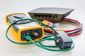 Network Tester And Small Switch With Various Color Rj45 Cables Connected For Testing