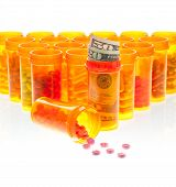 The High Cost Of Health Care.  Pills And Us Currency In Pill  Bottles Isolated On White.