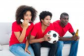 Nervous football fans in red sitting on couch on white background