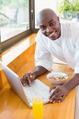 Happy man in bathrobe using laptop at breakfast at home in the kitchen