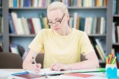 Student in glasses writing in library