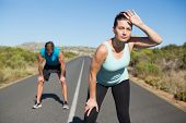 Fit couple jogging on the open road together on a sunny day