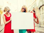 summer holidays, , travel, tourism and advertisement concept - three happy blonde women with blank w